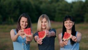 蓝色礼服的三个年轻可爱的妇女朋友在日落吃着西瓜和微笑 股票录像