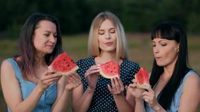 蓝色礼服的三个年轻可爱的妇女朋友在日落吃着西瓜和微笑 股票视频