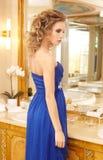 蓝色礼服的令人敬畏的白肤金发的妇女 免版税图库摄影