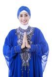 蓝色礼服的可爱的女性穆斯林在白色 免版税库存照片