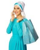 蓝色礼服的回教妇女有袋子和电话的 库存照片