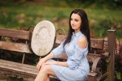 蓝色礼服的夫人坐长凳在湖附近 免版税图库摄影