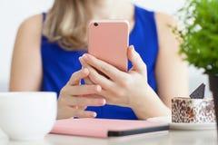 蓝色礼服的妇女在拿着桃红色电话的咖啡馆 免版税库存图片