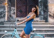 蓝色礼服的妇女在自行车 库存图片