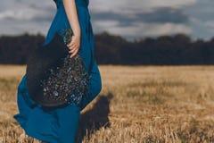 蓝色礼服的妇女有在她的手和花束步行的一个帽子的在黄色领域附近 免版税库存照片