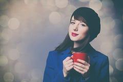 蓝色礼服的妇女有红色杯子的 免版税图库摄影