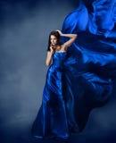 蓝色礼服的妇女有飞行的丝织物的 图库摄影