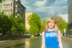 蓝色礼服的妇女金发碧眼的女人走沿城市街道的反对都市建筑学和夏天西伯利亚人秀丽背景  免版税库存图片