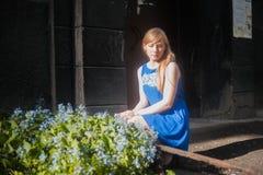 蓝色礼服的妇女金发碧眼的女人走沿城市街道的反对都市建筑学和夏天西伯利亚人秀丽背景  图库摄影
