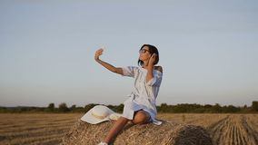 蓝色礼服的少妇享受在干草堆的自然在她的电话做美丽的selfie照片在托斯卡纳  影视素材
