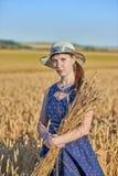蓝色礼服的少妇有麦子的小尖峰的在正面的麦田的- 免版税库存照片