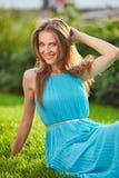 蓝色礼服的年轻美丽的微笑的妇女坐一个绿色草甸在城市公园 免版税库存照片