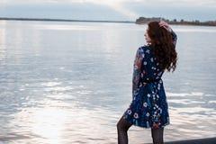 蓝色礼服的年轻美丽的深色的妇女在秋天河堤防 免版税图库摄影