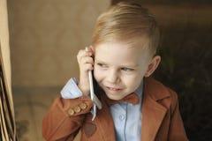 蓝色礼服的微笑的十几岁的女孩谈话在手机,绿色夏天公园 免版税库存照片