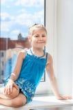 蓝色礼服的微笑的幼儿是在太阳光的窗口基石 免版税库存照片