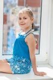蓝色礼服的愉快的女孩坐在太阳光的窗台 库存图片