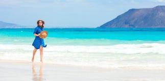 蓝色礼服的愉快的旅行家妇女享受她的热带海滩假期 库存照片