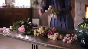 蓝色礼服的无法认出的女性卖花人安排在桌上的花,为未来构成做准备 股票录像