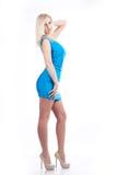 蓝色礼服的白肤金发的妇女在白bg 免版税库存照片