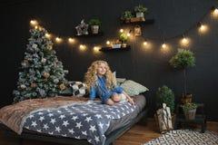 蓝色礼服的白肤金发的小女孩坐一张床在圣诞节暗室 免版税库存照片