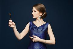 蓝色礼服的美丽和时髦年轻深色的妇女在她的手上拿着构成刷子 免版税库存照片