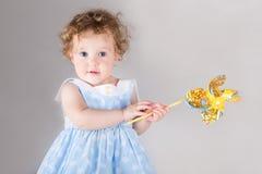 蓝色礼服的美丽的卷曲女婴有风玩具的 库存图片