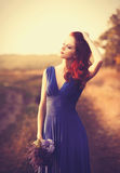 蓝色礼服的美丽的女孩有花束的 图库摄影
