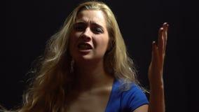 蓝色礼服的美丽的性感的白肤金发的女孩是唱歌和跳舞在演播室有黑背景 免版税图库摄影