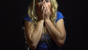 蓝色礼服的美丽的性感的白肤金发的女孩是高兴和满意的在演播室有黑背景 股票录像