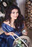 蓝色礼服的美丽的深色的妇女在新年装饰了int 免版税图库摄影