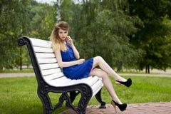 蓝色礼服的美丽的白肤金发的女孩坐一条长凳在夏天 库存图片