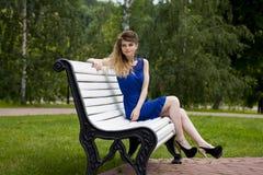 蓝色礼服的美丽的白肤金发的女孩坐一条长凳在夏天 免版税图库摄影