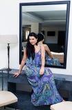 蓝色礼服的美丽的年轻深色的妇女 图库摄影