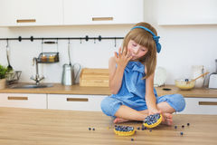 蓝色礼服的逗人喜爱的小女孩吃一个蛋糕并且舔她的在桌上的手指 免版税图库摄影