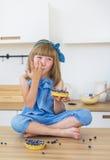 蓝色礼服的逗人喜爱的小女孩吃一个蛋糕并且舔她的手指 免版税库存照片
