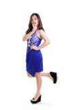蓝色礼服诱人的姿势的逗人喜爱的女孩 免版税库存照片