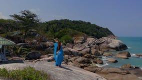 蓝色礼服跳舞的空中寄生虫视图妇女在峭壁部族融合背景海,平房 影视素材