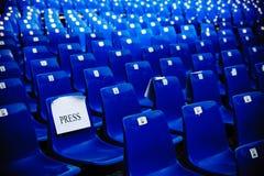 蓝色空的椅子行在新闻的一个会议大厅里 免版税库存图片