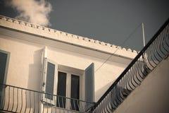 蓝色窗口在葡萄酒口气的五颜六色的天空下 免版税库存照片