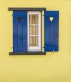 蓝色窗口细节与心脏和黄色墙壁的 免版税库存图片