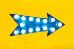 蓝色箭头塑造了与发光的电灯泡的葡萄酒五颜六色的被阐明的金属显示方向标在生动的黄色墙壁上 免版税库存照片
