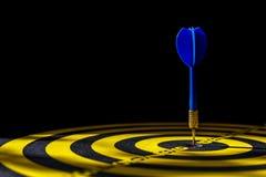 蓝色箭箭头在掷镖的圆靶的中心 查出在黑色 免版税库存图片