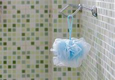 蓝色纤维垂悬在路轨的Scrub在有绿色的卫生间里 免版税库存图片