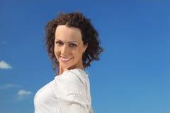 蓝色纵向天空微笑的妇女 免版税库存图片