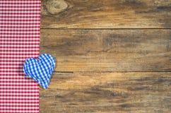 蓝色织品心脏和红色方格的织品在土气木头 免版税库存照片