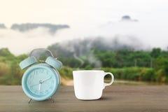 蓝色经典闹钟和热的加奶咖啡杯子有蒸汽的在葡萄酒木书桌上在被弄脏的有雾的山背景 图库摄影