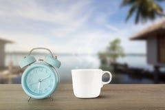 蓝色经典闹钟和热的加奶咖啡杯子有蒸汽的在葡萄酒木书桌上在被弄脏的海滩背景 图库摄影