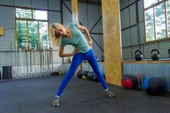 蓝色绑腿的白肤金发的女孩在健身房训练,站立a 库存照片