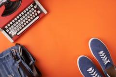 蓝色绒面革运动鞋鞋子、困厄的牛仔裤和打字机在橙色背景 库存照片