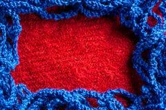 蓝色编织了在红色织品背景的螺纹 图库摄影